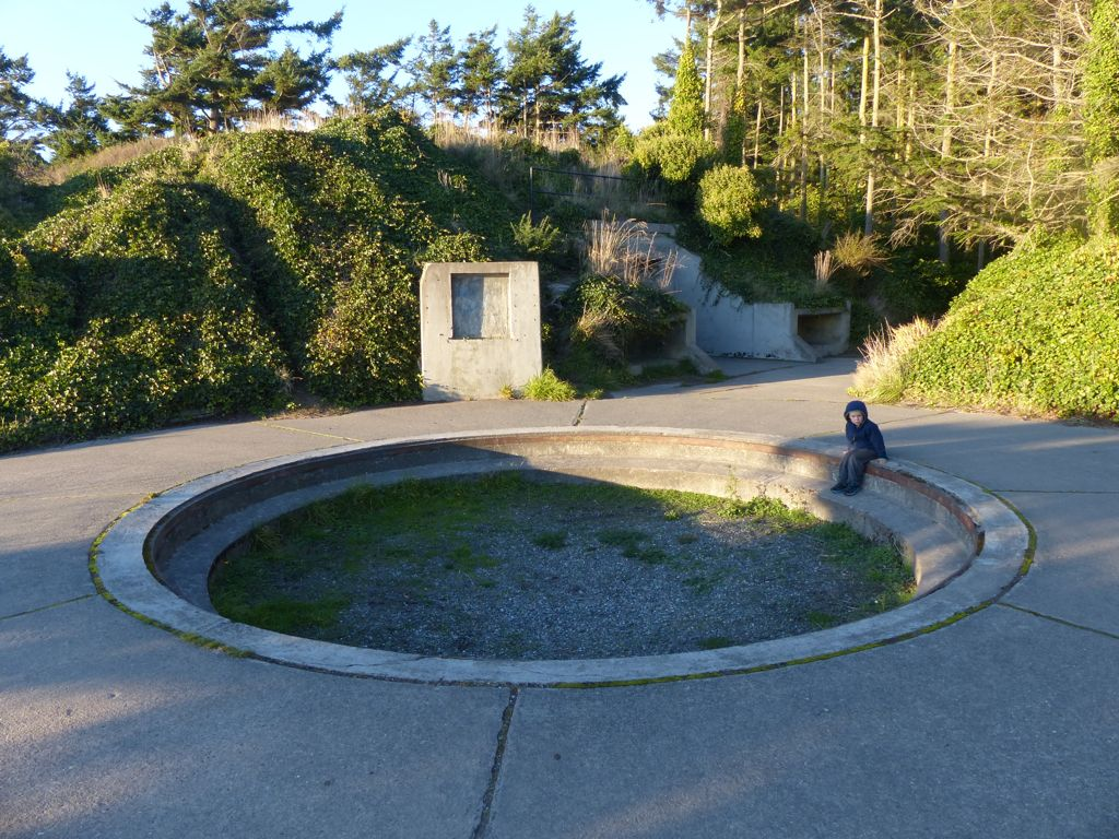 Quinn sits in the foundation for one of the WWII guns at Fort Ebey. The entrance to the bunker is in the background.