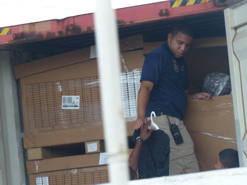 While waiting at the port I had the opportunity to watch customs officials helping themselves to the contents of trucks. This guy is snagging a nice new shirt for his buddy.