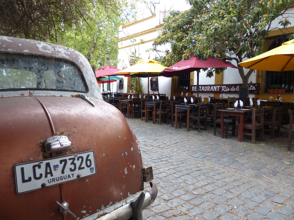 The streets of Colonia feature sidewalk restaurants, shade trees, and classic cars